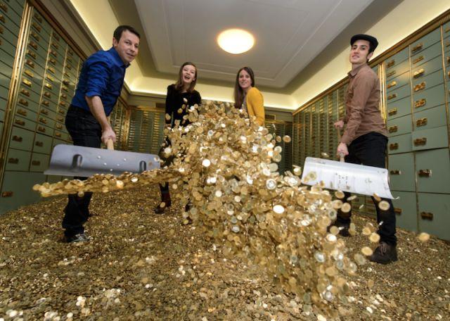 4 personnes munies de pelles, à l'intérieur d'un coffre-fort, soulèvent des tas de pièces d'or