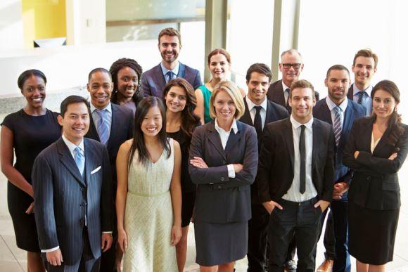 Un groupe d'employés de bureau font un grand sourire à la caméra.