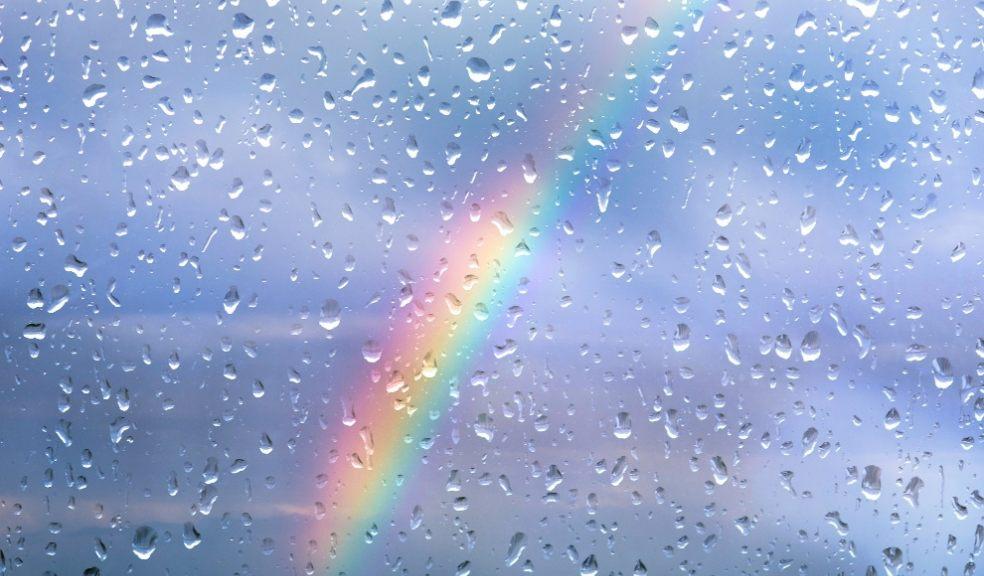 Un arc-en-ciel en arrière-plan d'une vitre pleine de gouttes d'eau.