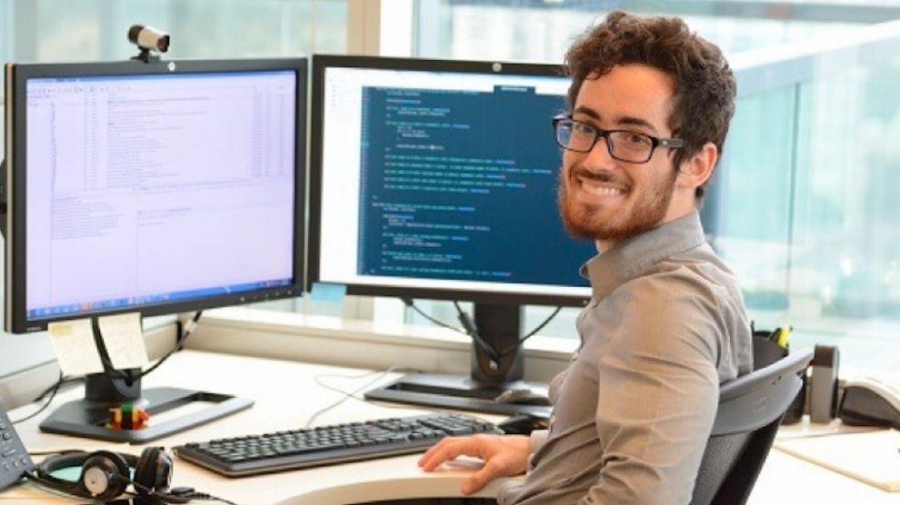 Un homme, devant deux écrans contenant vraisemblablement du code, fait face à la caméra avec un grand sourire.