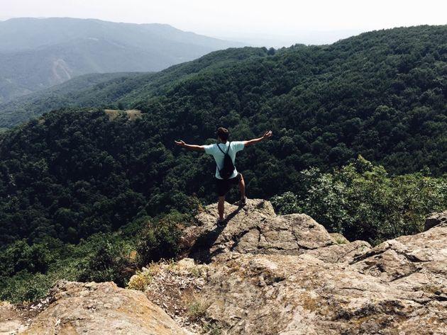 Un homme en tenue de randonneur, les bras écartés, se tient en haut d'une falaise.