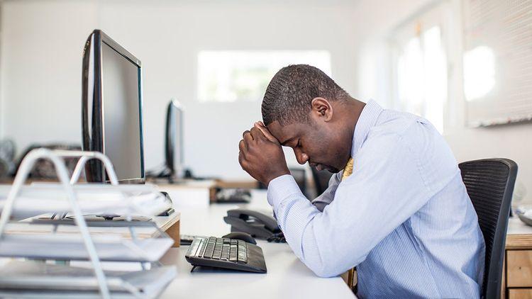 Un homme, devant un écran, a la tête entre les mains, visiblement stressé.