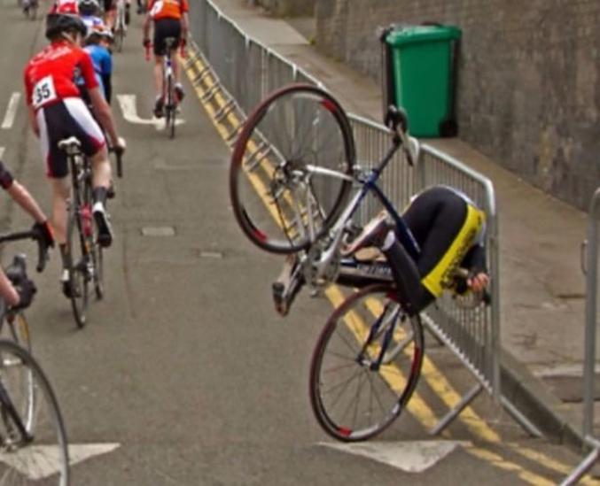 Un coureur cycliste fonce la tête la première dans une barrière le long de la route.