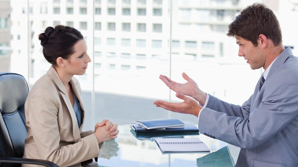 Un jeune homme en costume lavande est en pleine discussion avec une jeune femme ; on a l'impression qu'il jongle avec ses mains