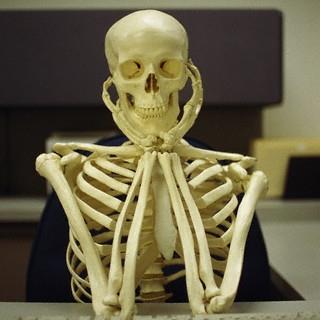 Un squelette, le menton posé sur les mains, attend quelque chose