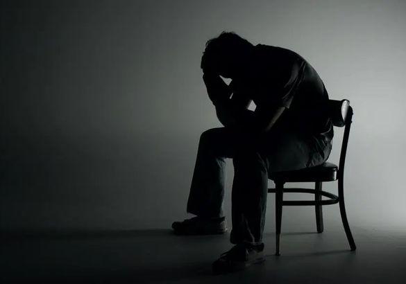 Un homme seul sur une chaise et dans la pénombre, se prend la tête entre les mains.