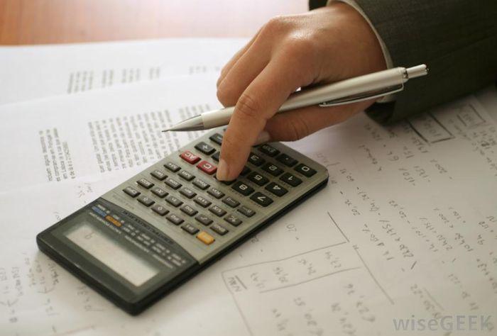 Une main tenant un stylo argenté tape sur une calculatrice. On voit aussi des papiers pleins de calculs.